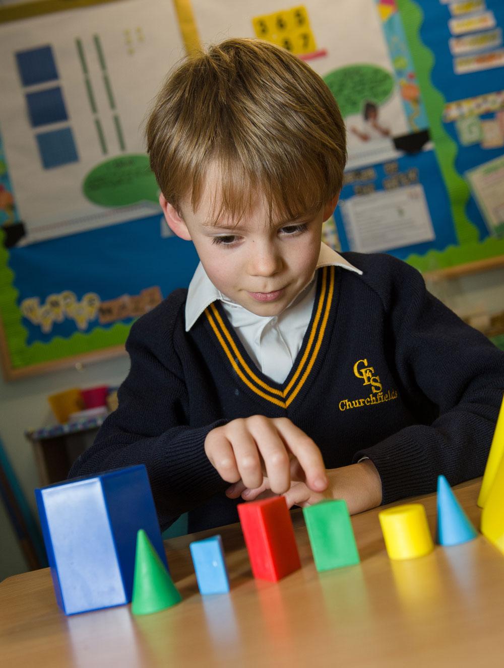Boy pointing at green geometric shape