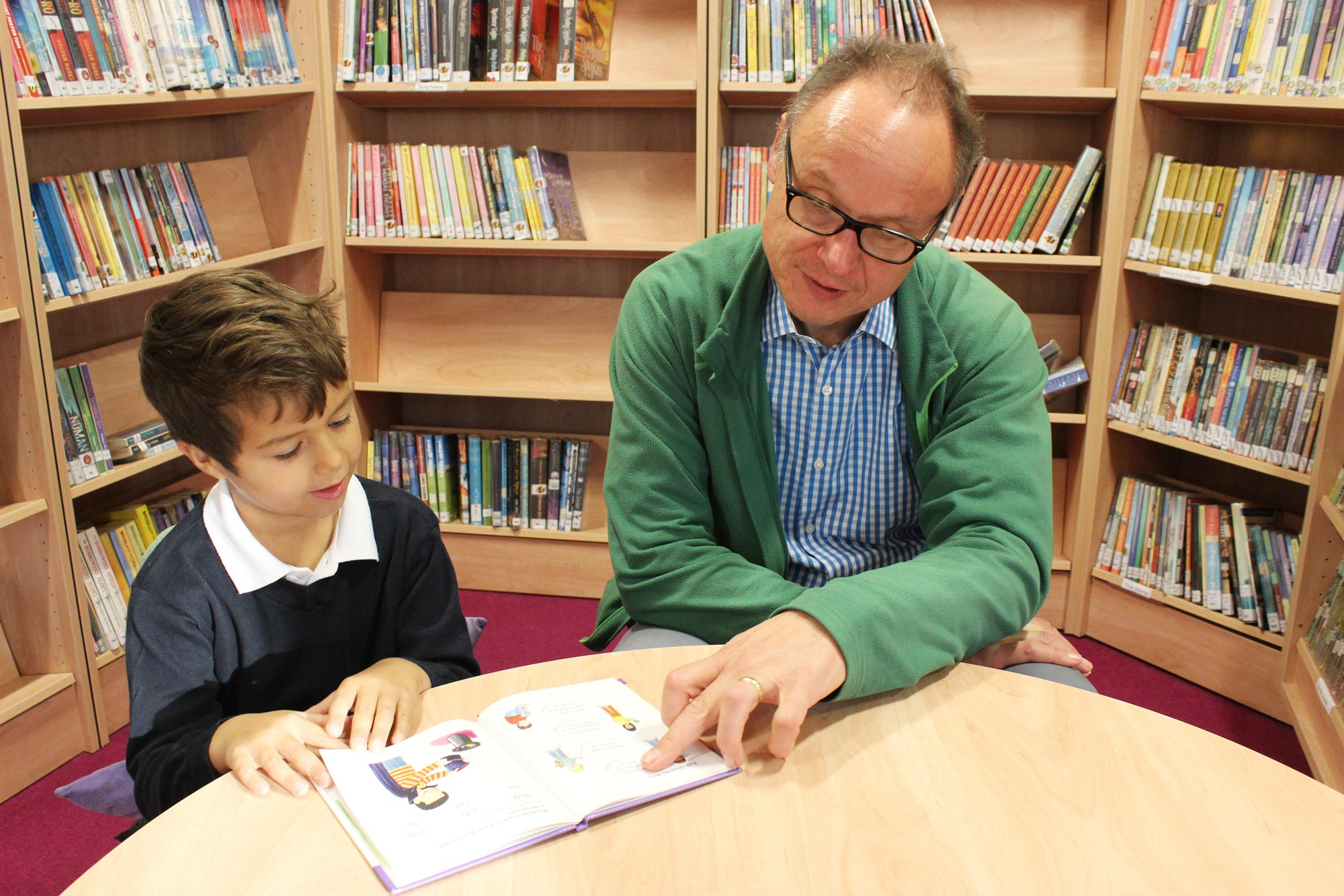 Parent helps pupil with reading