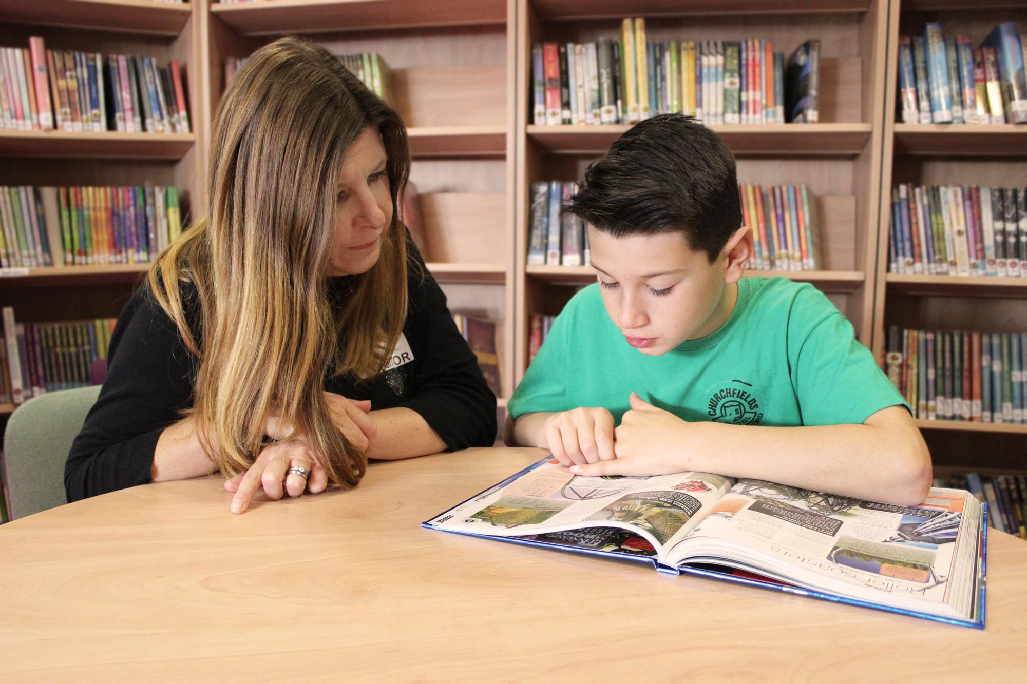 Parent helping pupil with reading