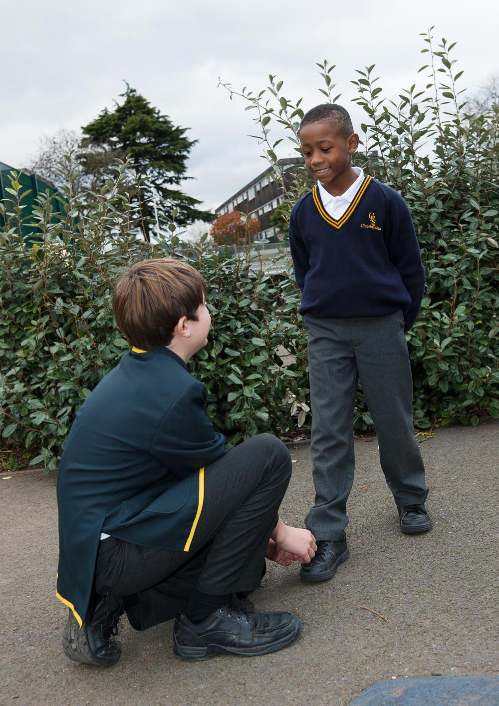 Boy tying friend's shoelaces