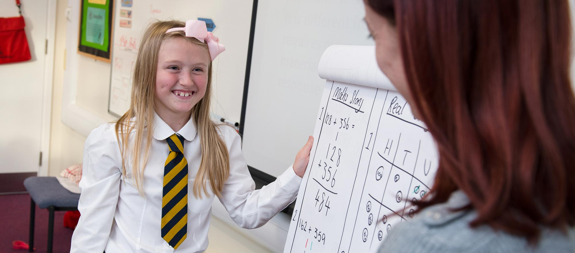 Smiling girl showing her maths skills to the teacher
