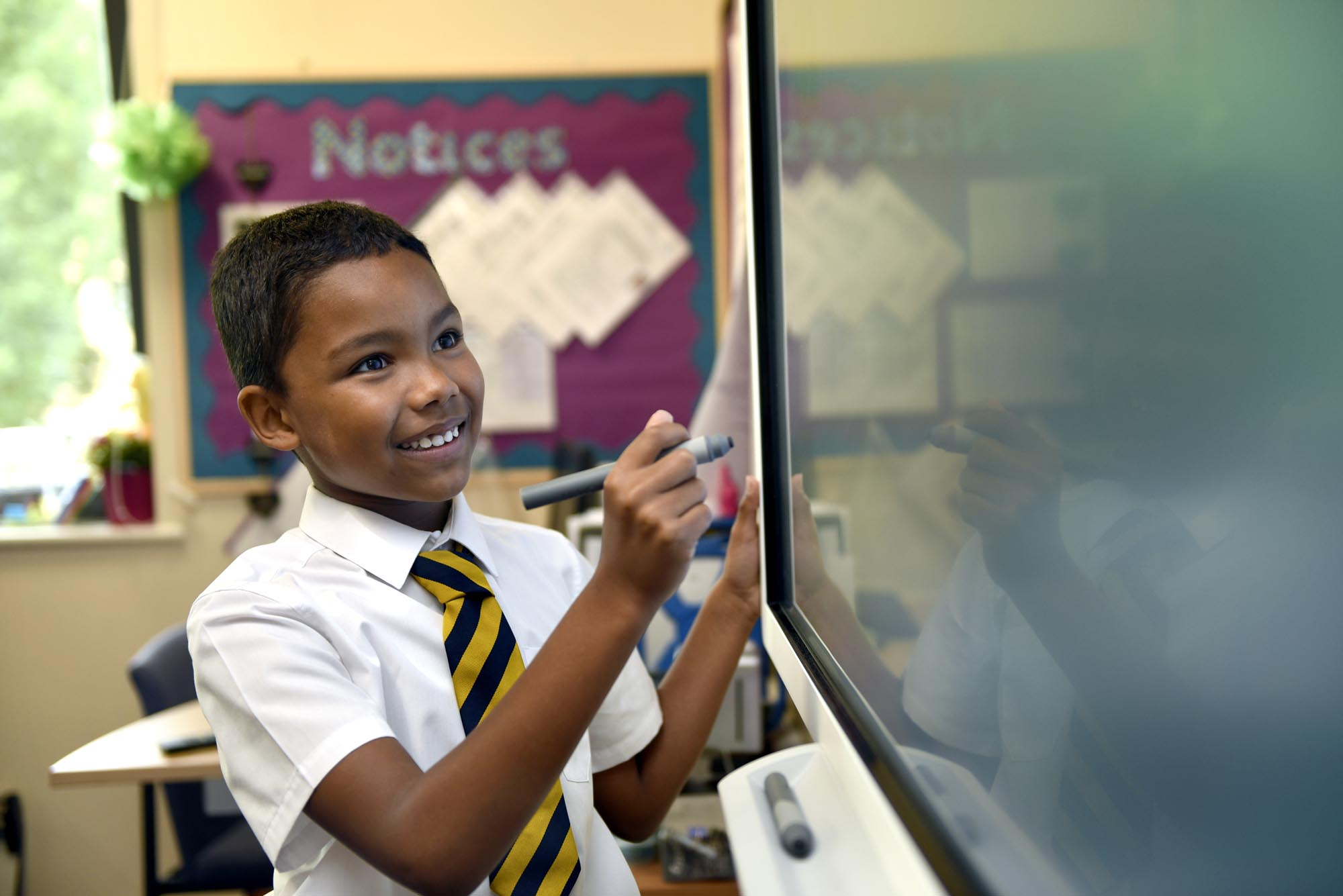 Boy writing on interactive board