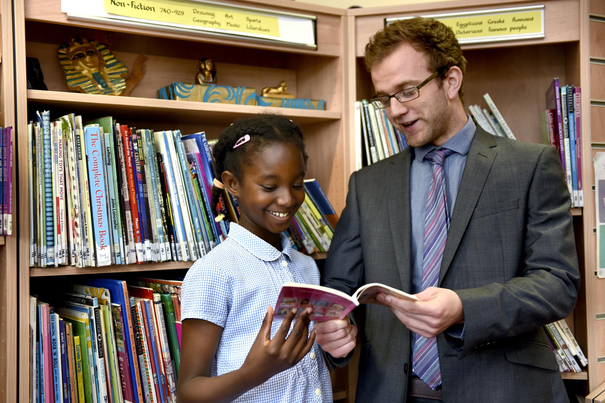 Teacher and pupil reviewing book in the library.