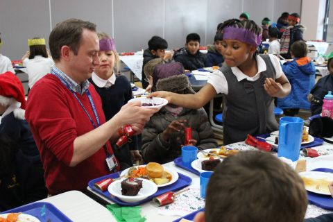 Pupils and teacher in dining hall enjoying Christmas dinner