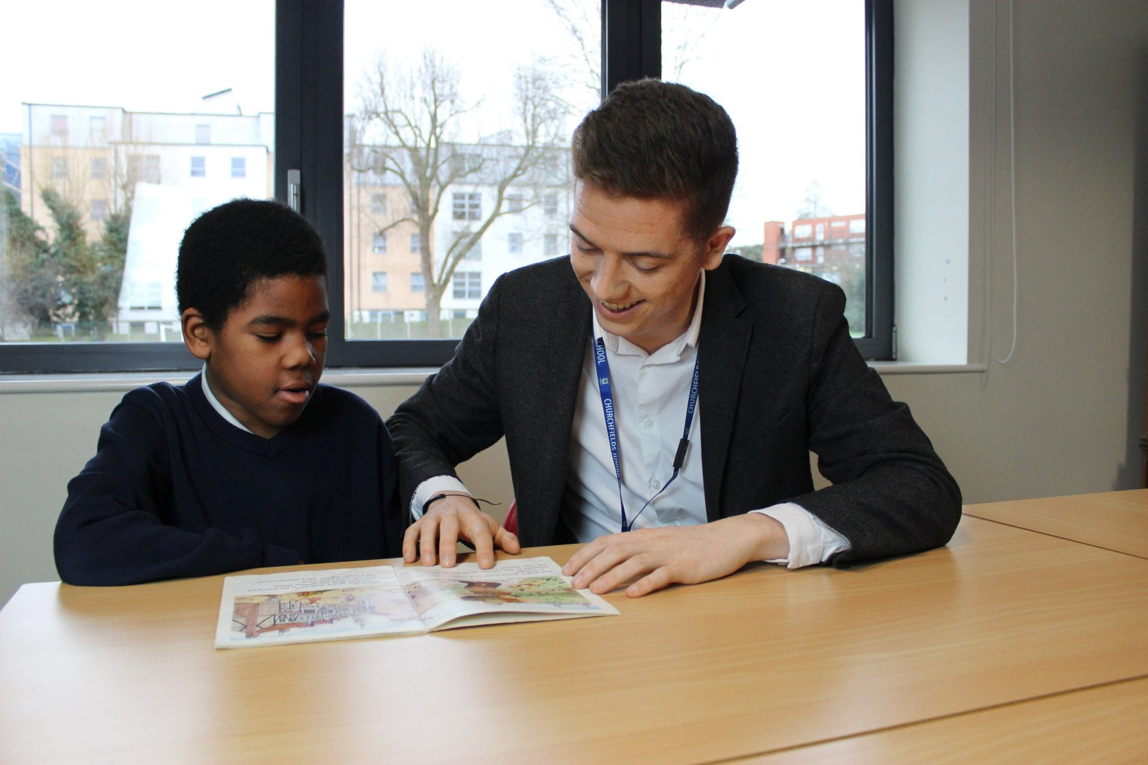 Mr Webster and pupil reading book