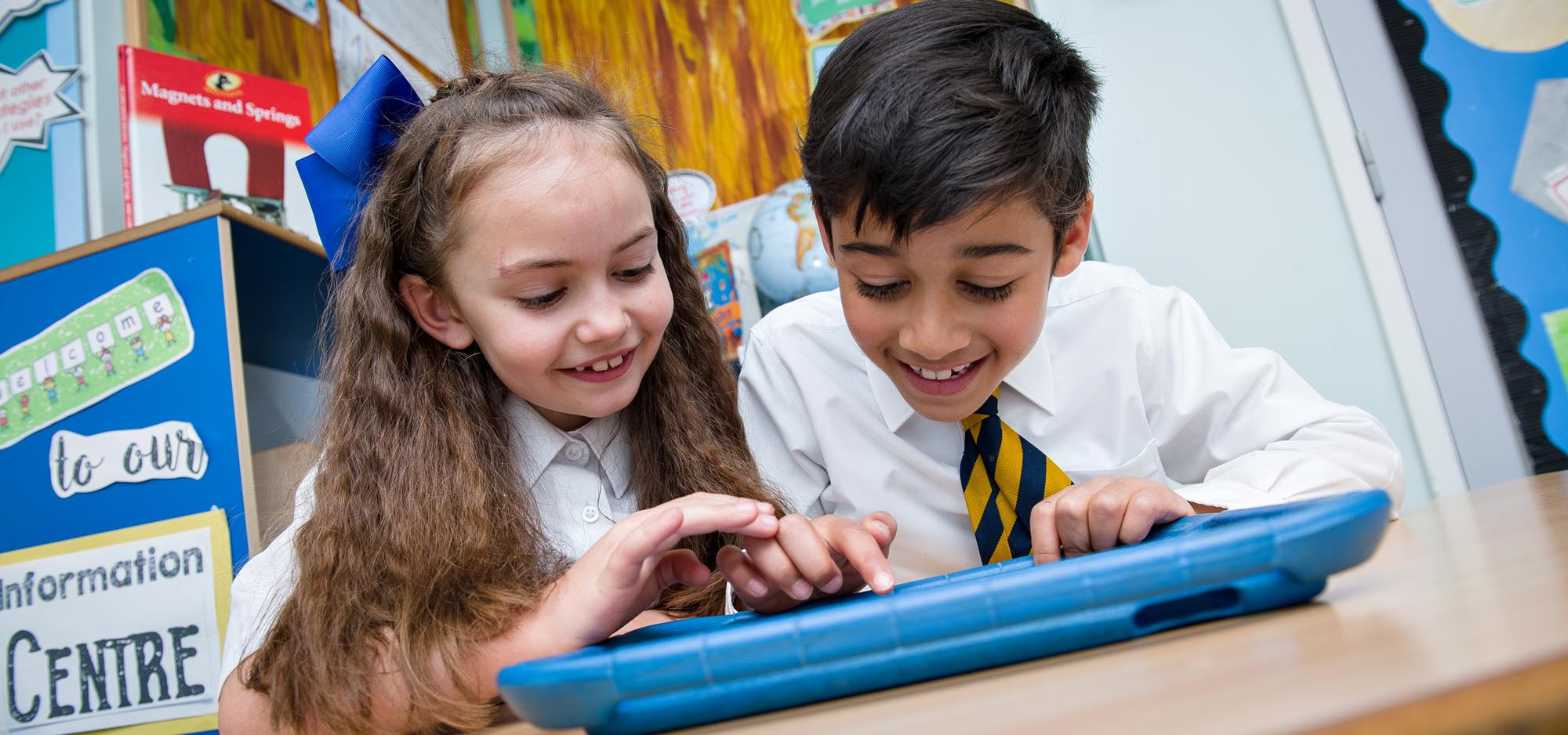 Girl and boy using apps on tablet