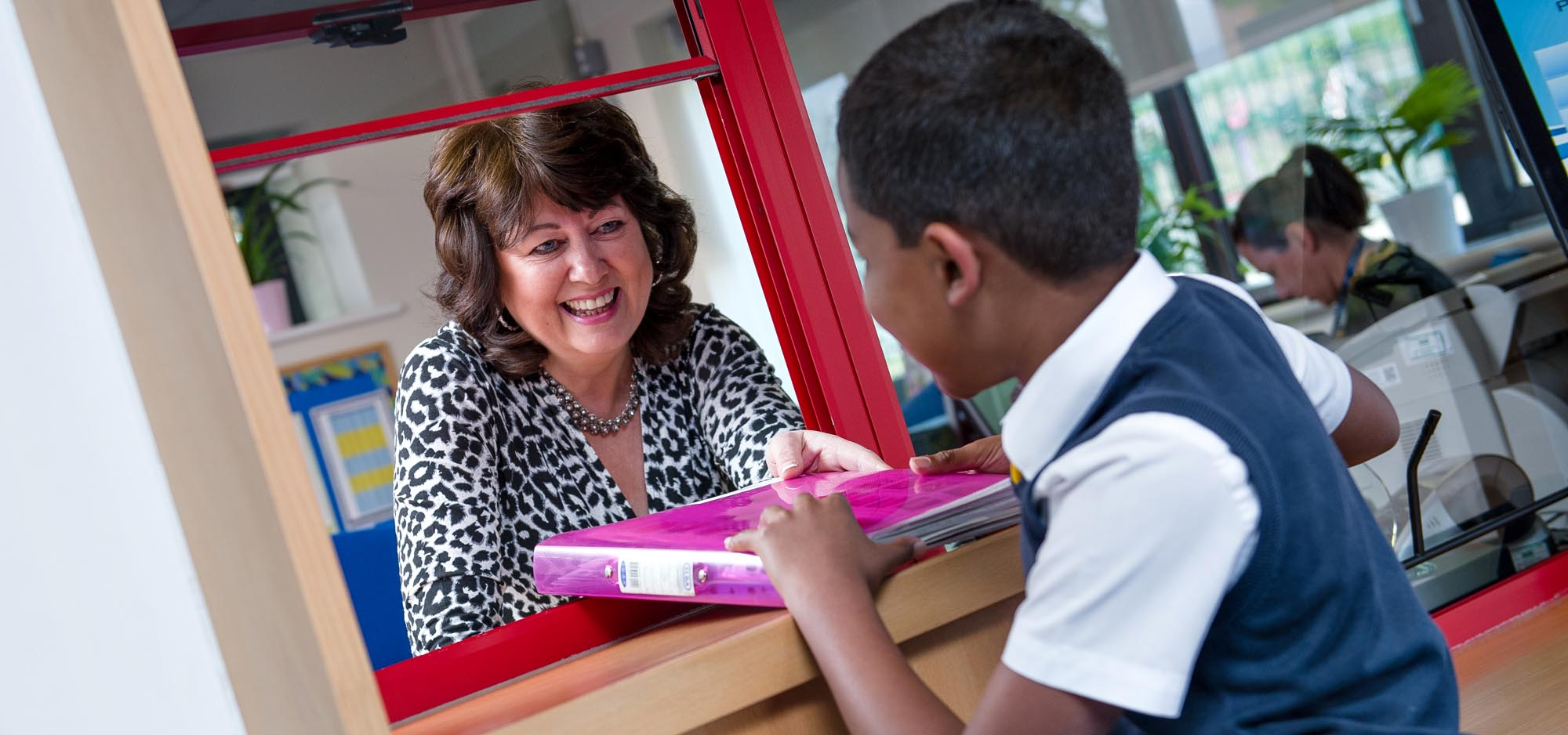 Mrs Drinkwater passing ringbinder to pupil