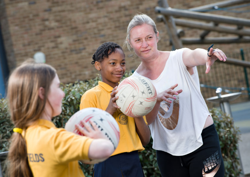 Miss Brown teaching two girls to play netball