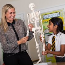 Teacher and child looking at skeleton model