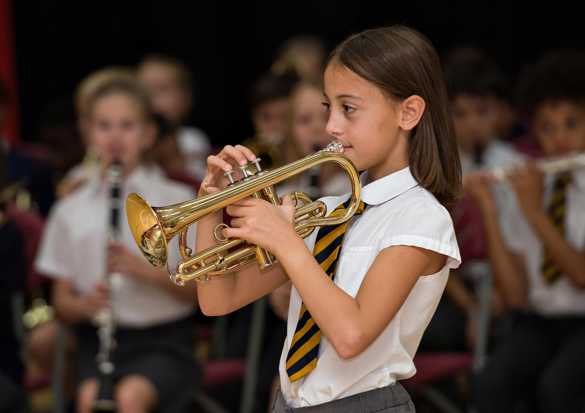 Girl playing cornet with orchestra in the background