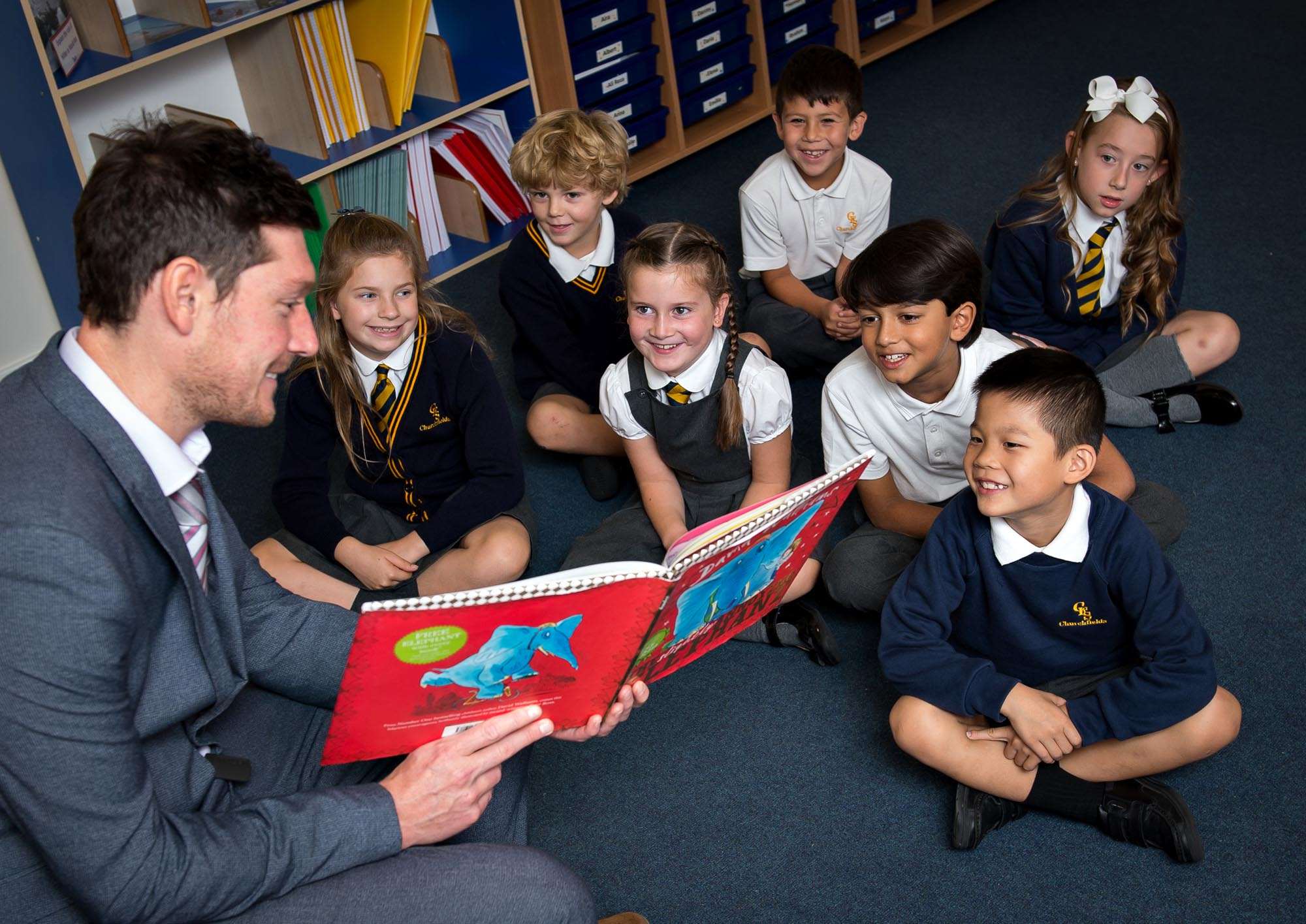Mr Warmoth reading a book for children sitting on the floor