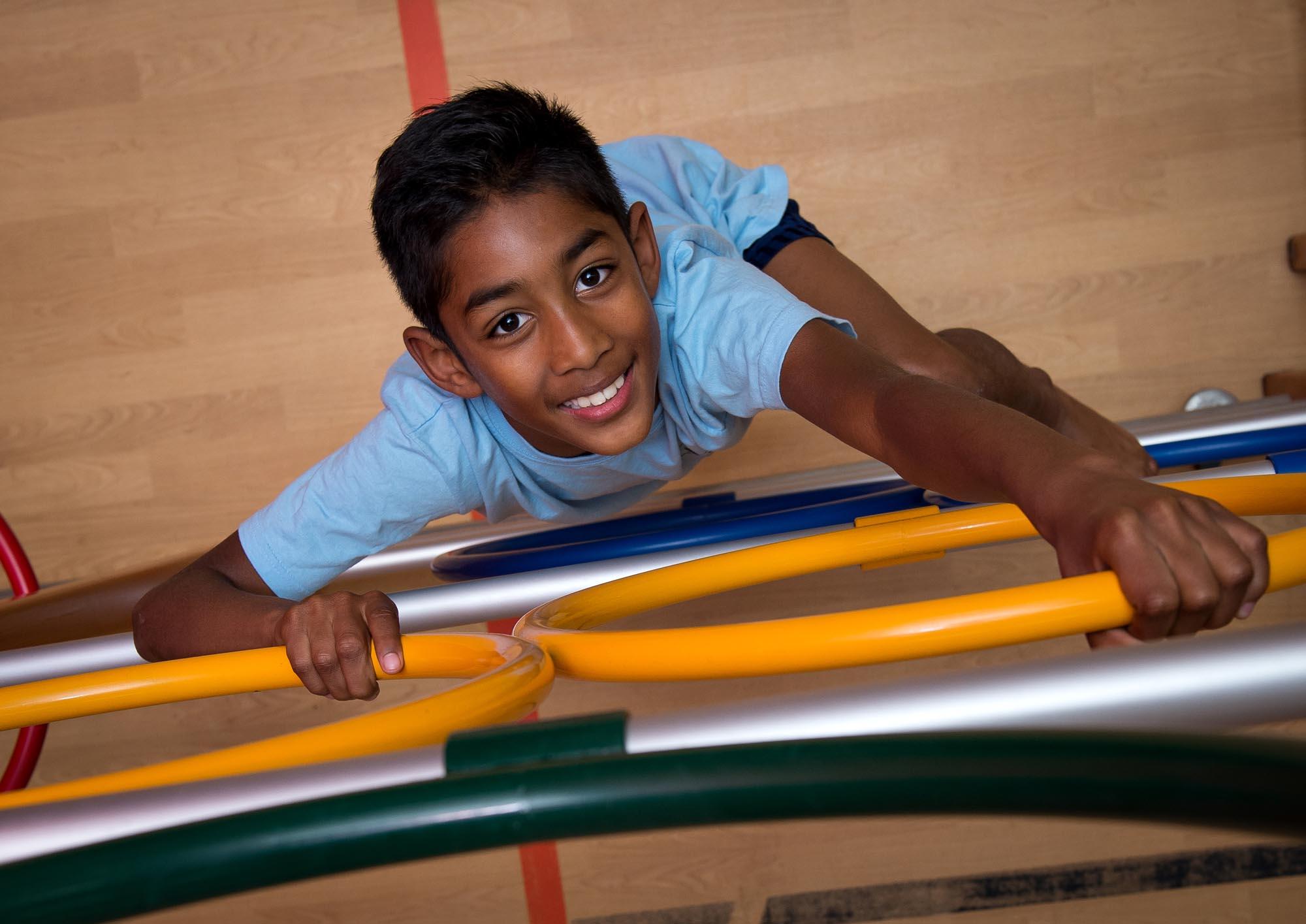 Boy climbing up indoor apparatus landscape