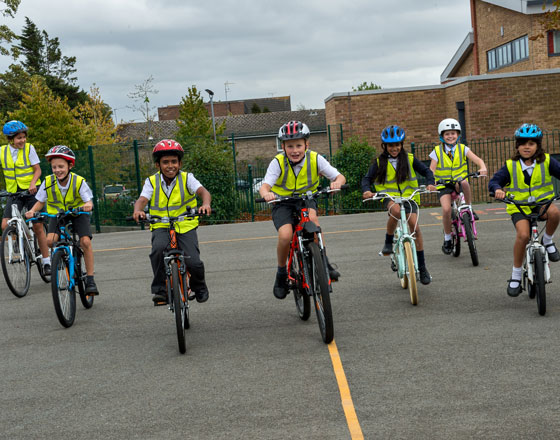 Children with yellow vests cycling in playground