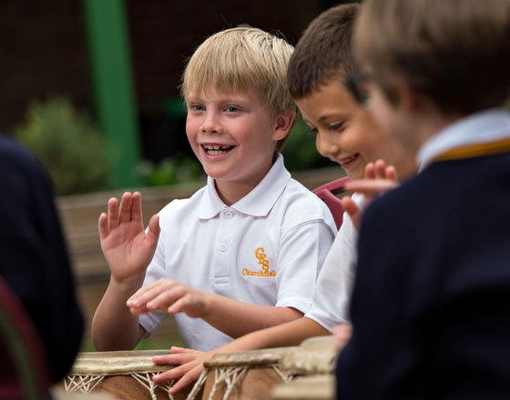 Boy drumming together with other pupils