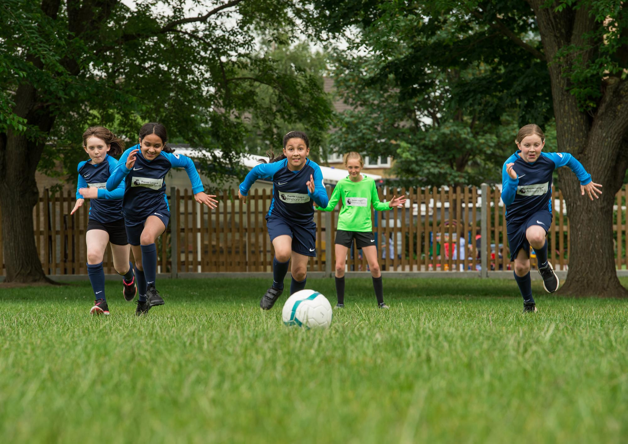 Girls playing football, running towards ball
