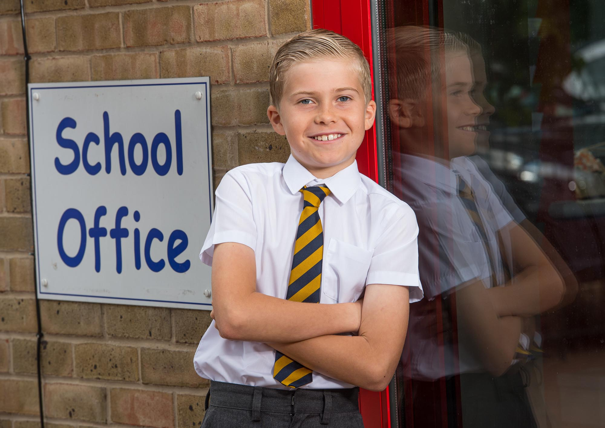 Boy leaning towards wall outside school office