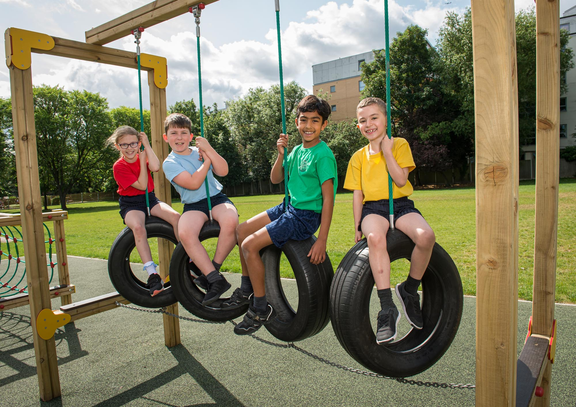 Four children playing on tyres