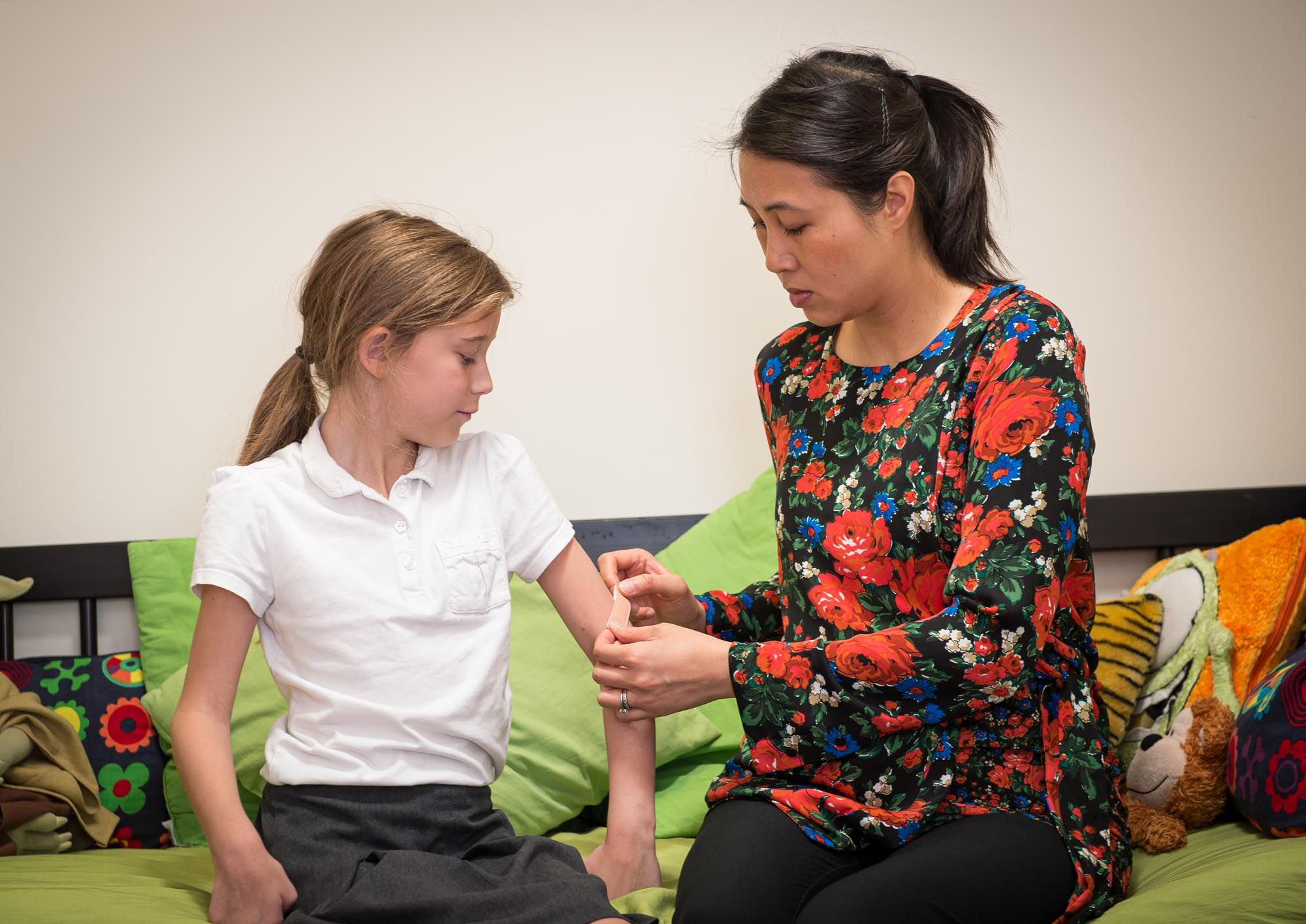 Putting on a plaster on girl's arm