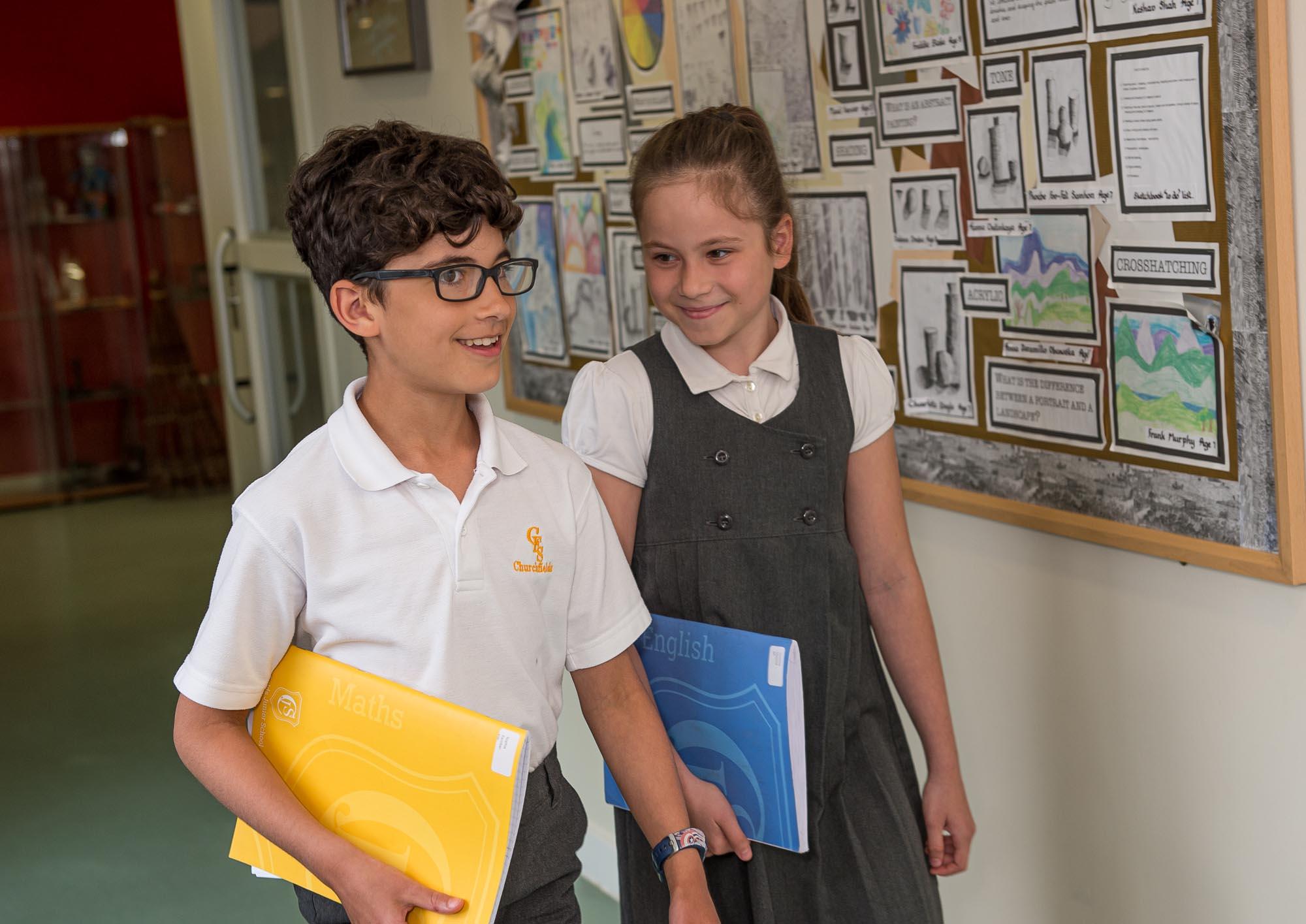 Boy and girl walking past display in corridor