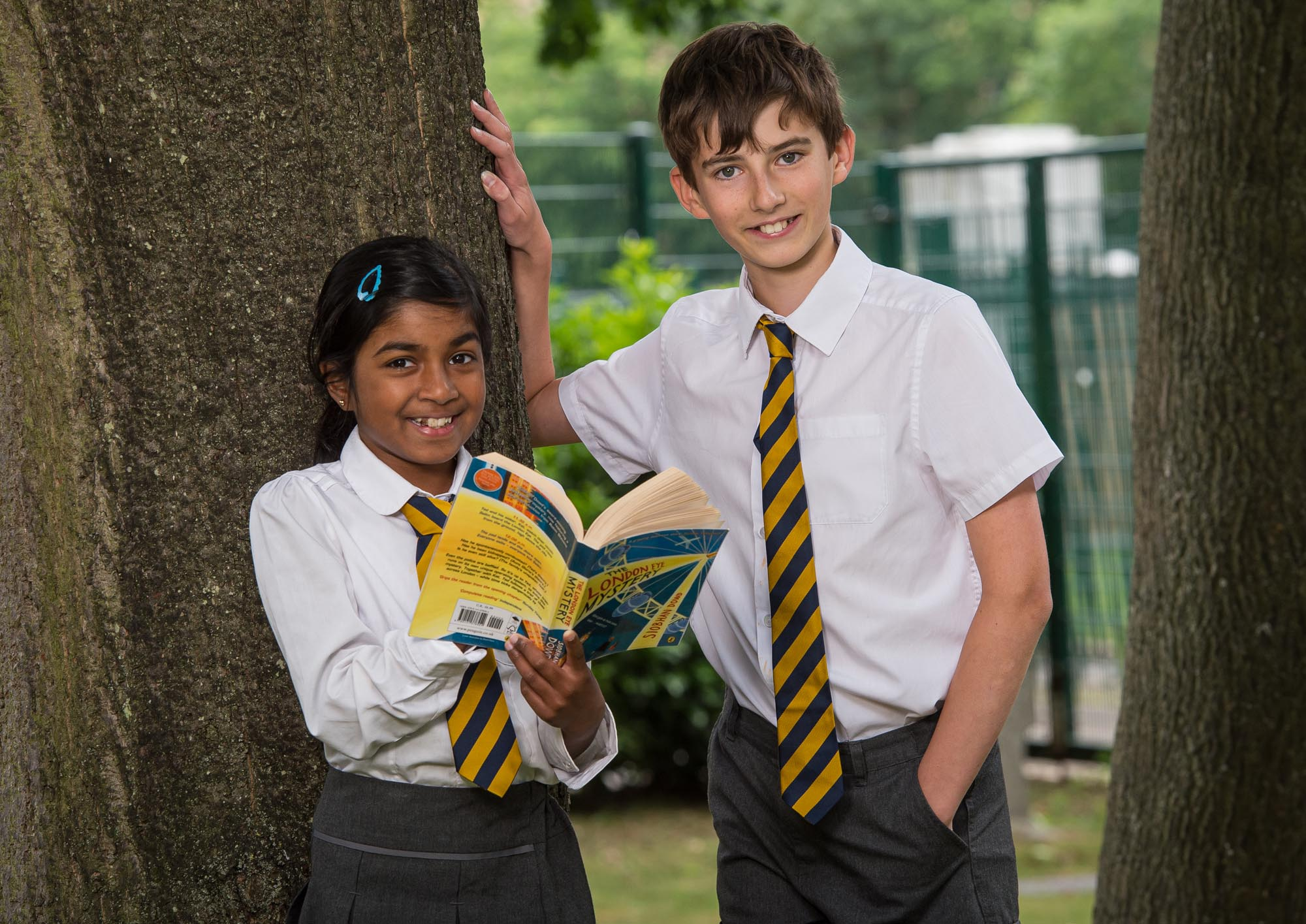 Boy and girl by tree reading book