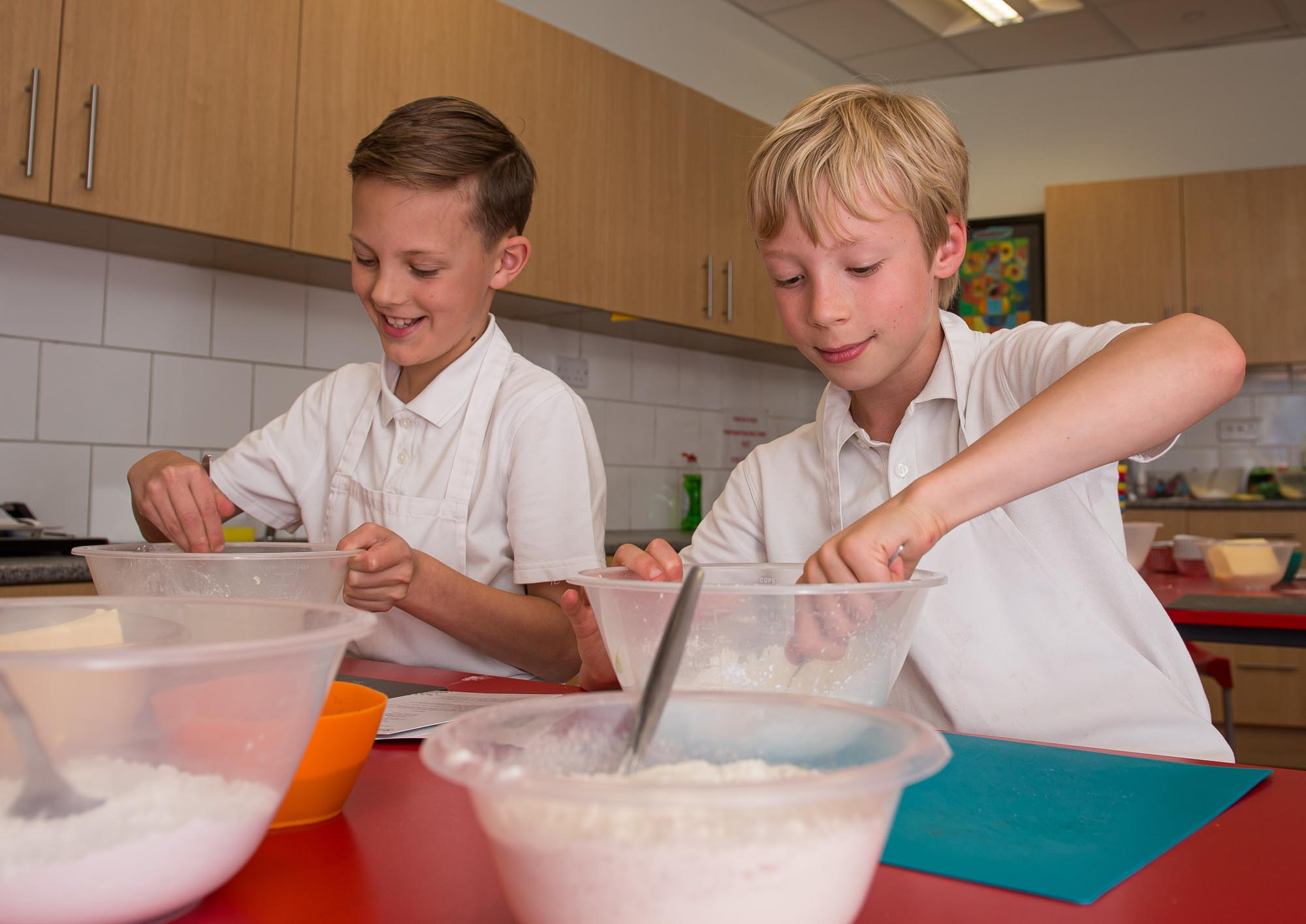 Two boys mixing flour in bowls