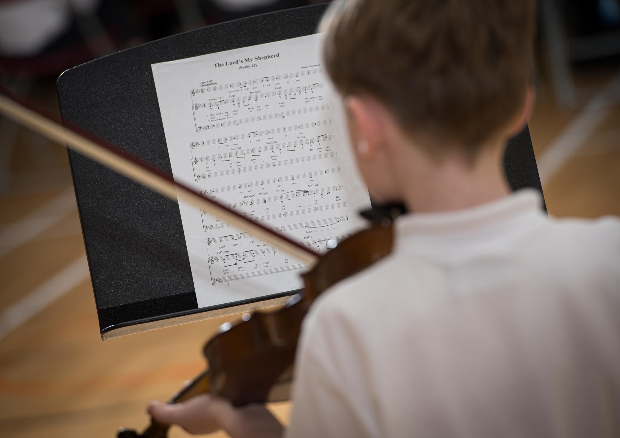 Boy playing violin looking at music notes