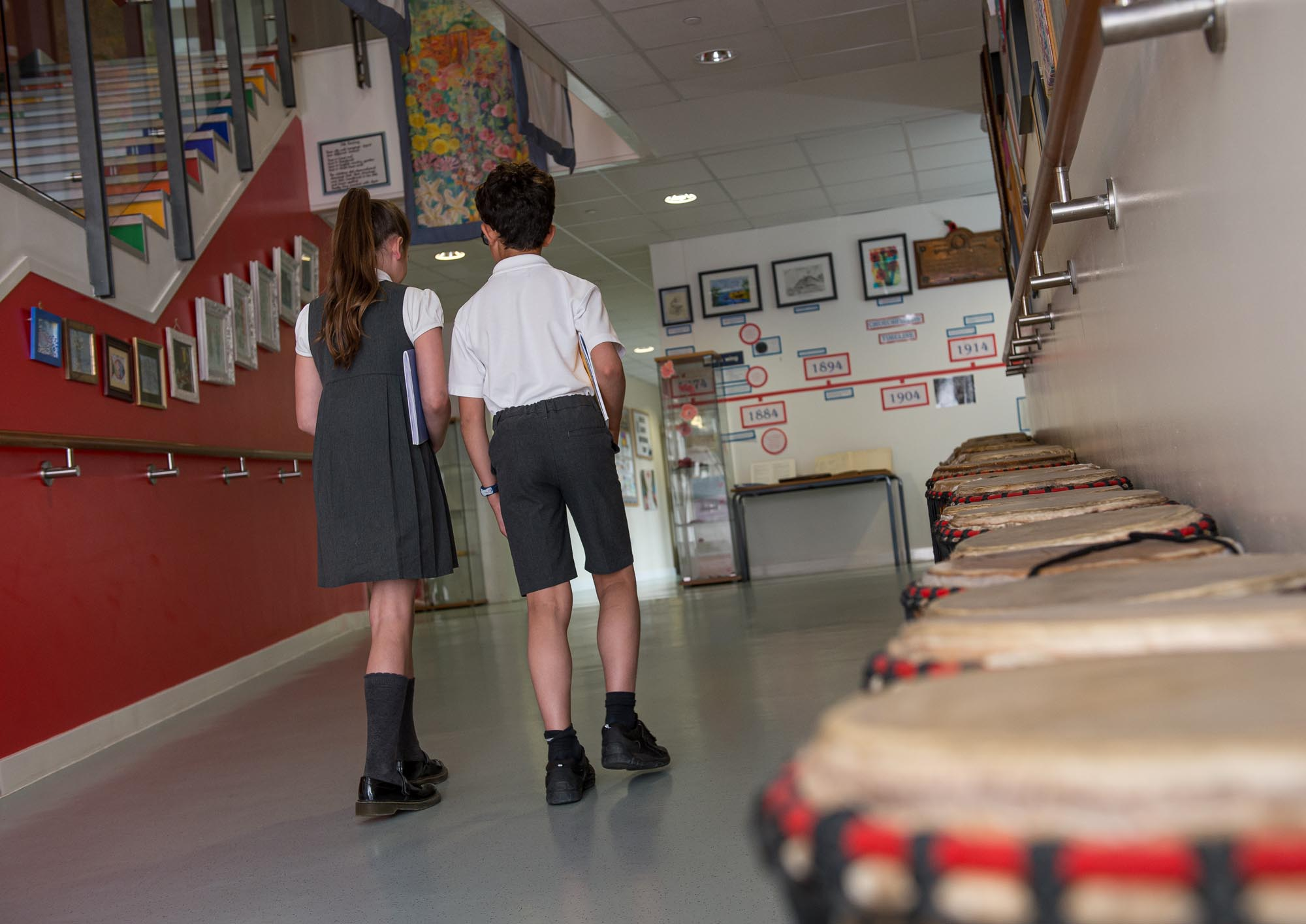 Two pupils walking down corridor