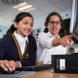 Two girls looking and pointing at computer screen