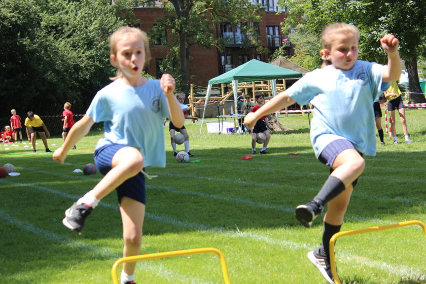 Two girls jumping over hurdles