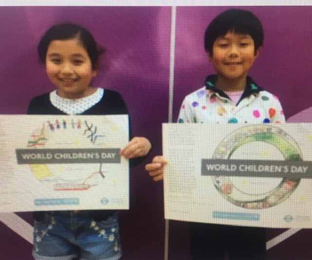 "Two children holding up ""World Children's Day"" signs"
