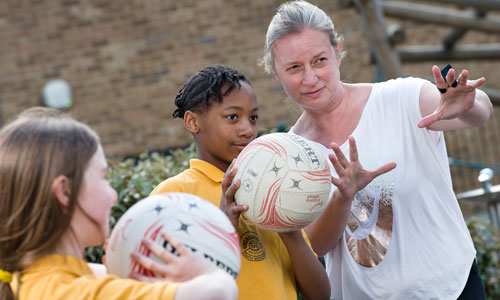 PE teacher showing pupil how to throw netball