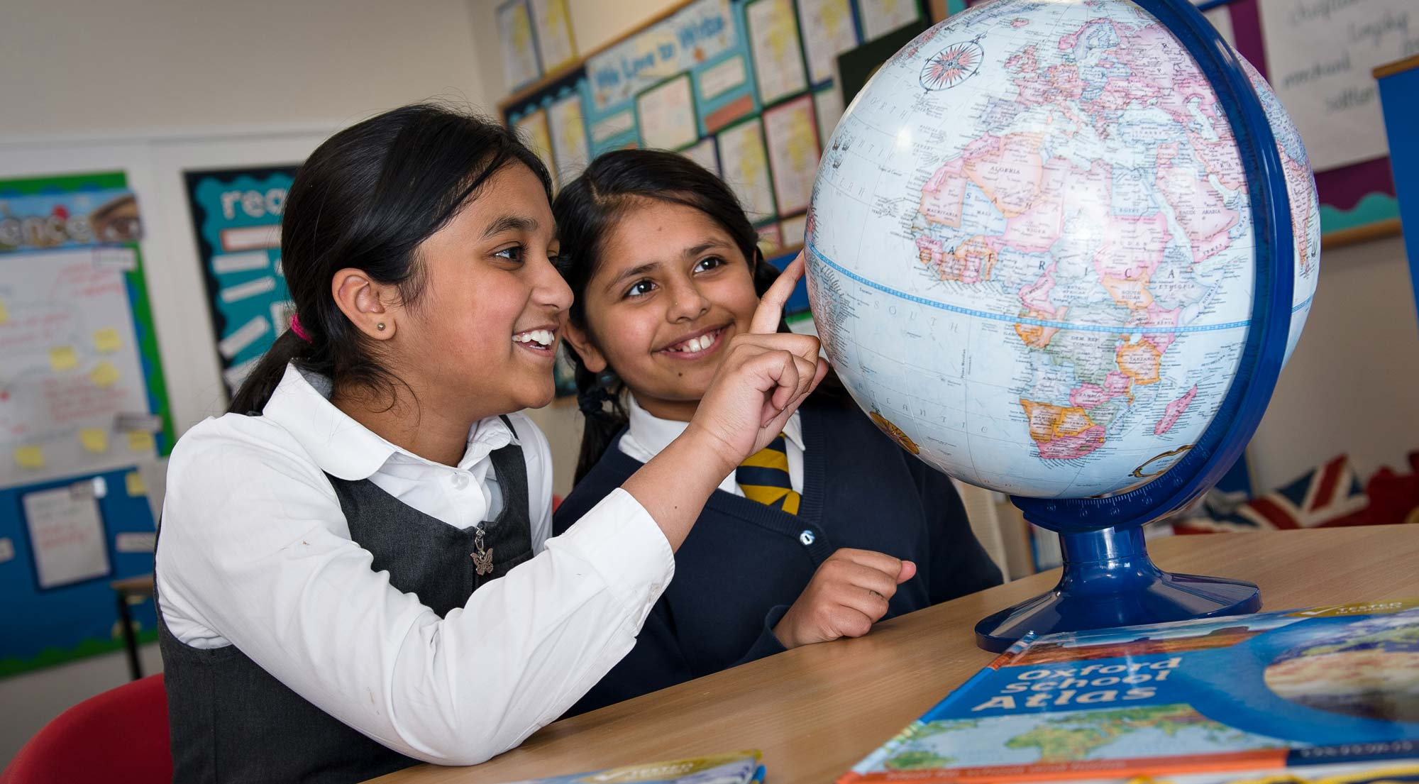 Two smiling girls pointing at globe