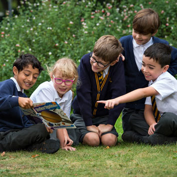 Children-sitting-on-the-grass-reading-a-book_500
