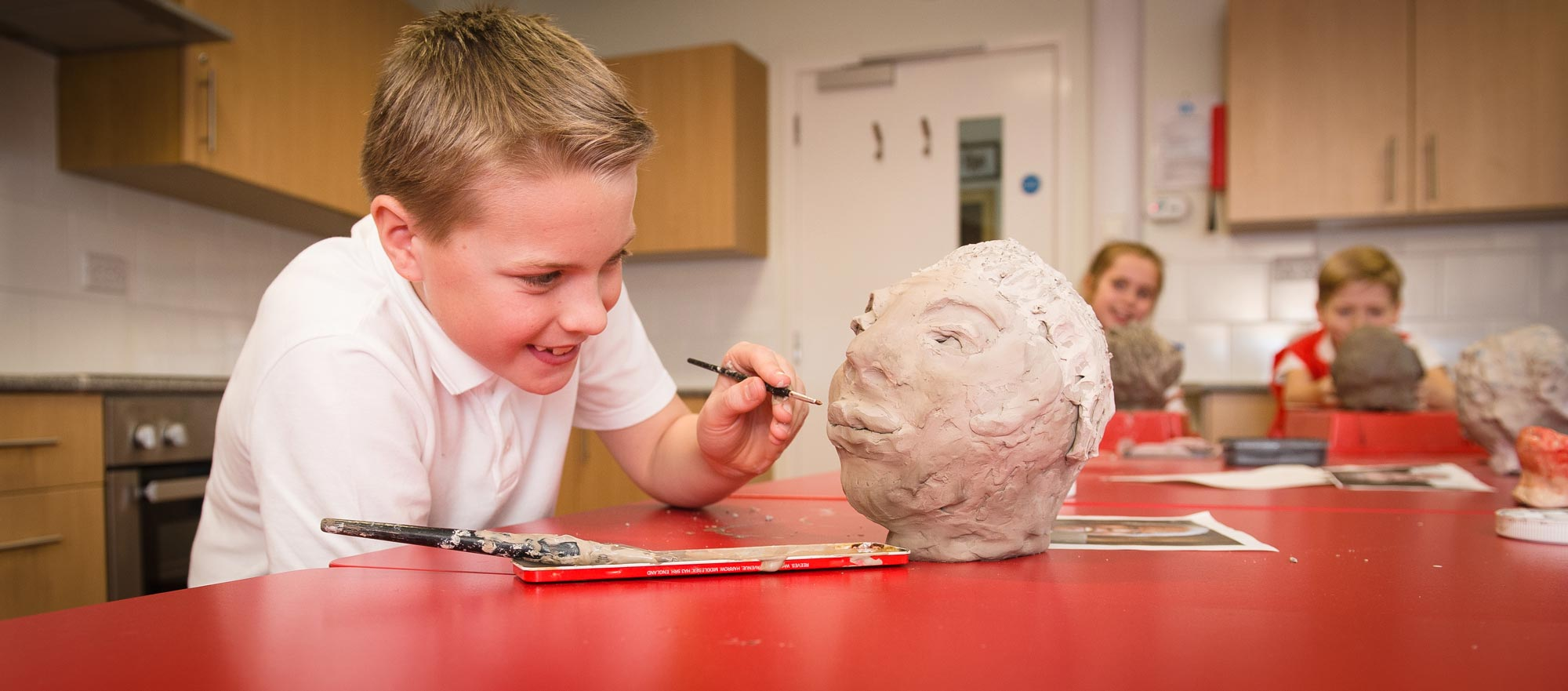 Boy adding detail to his clay sculpture