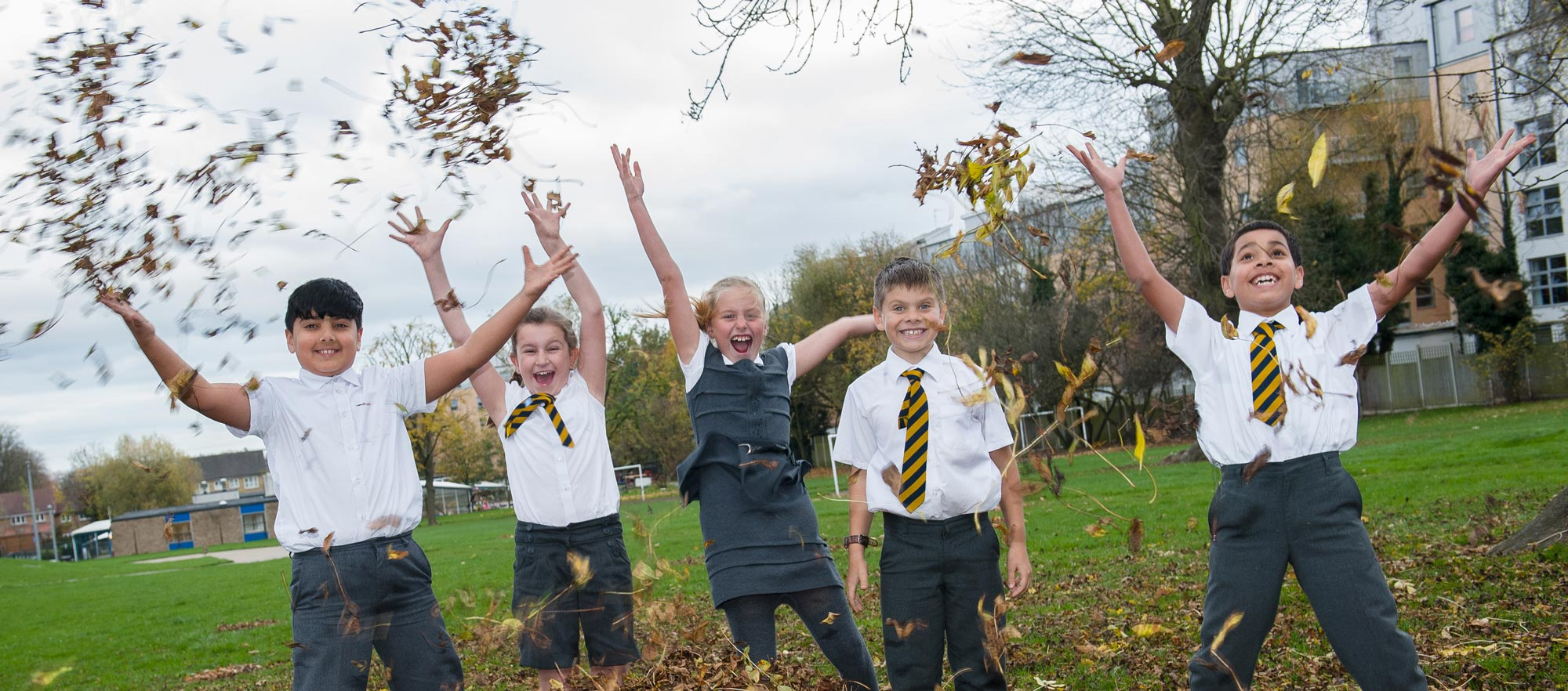 Children throwing autumn leaves in the air
