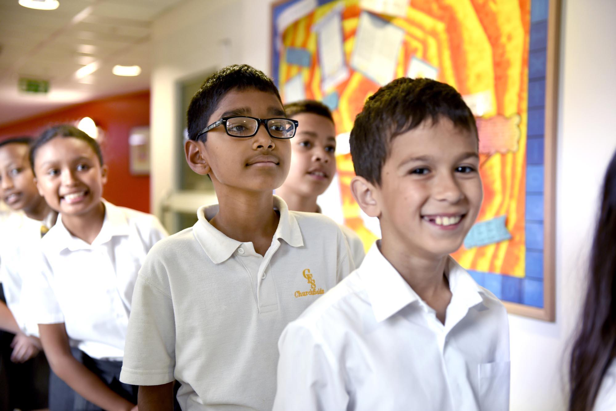 Pupils standing in line in corridor