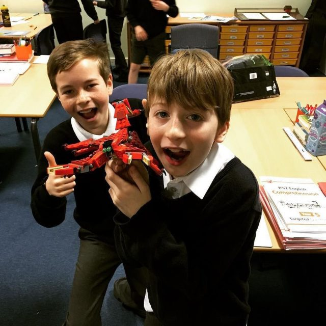 Two boys holding a lego figure