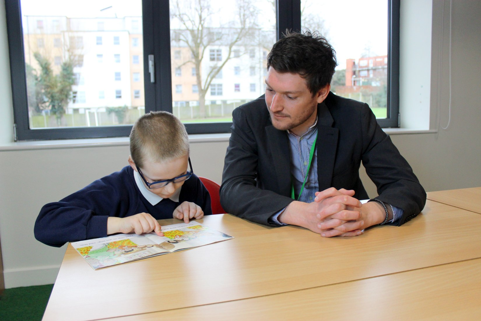 Mr Warmoth and pupil reading book
