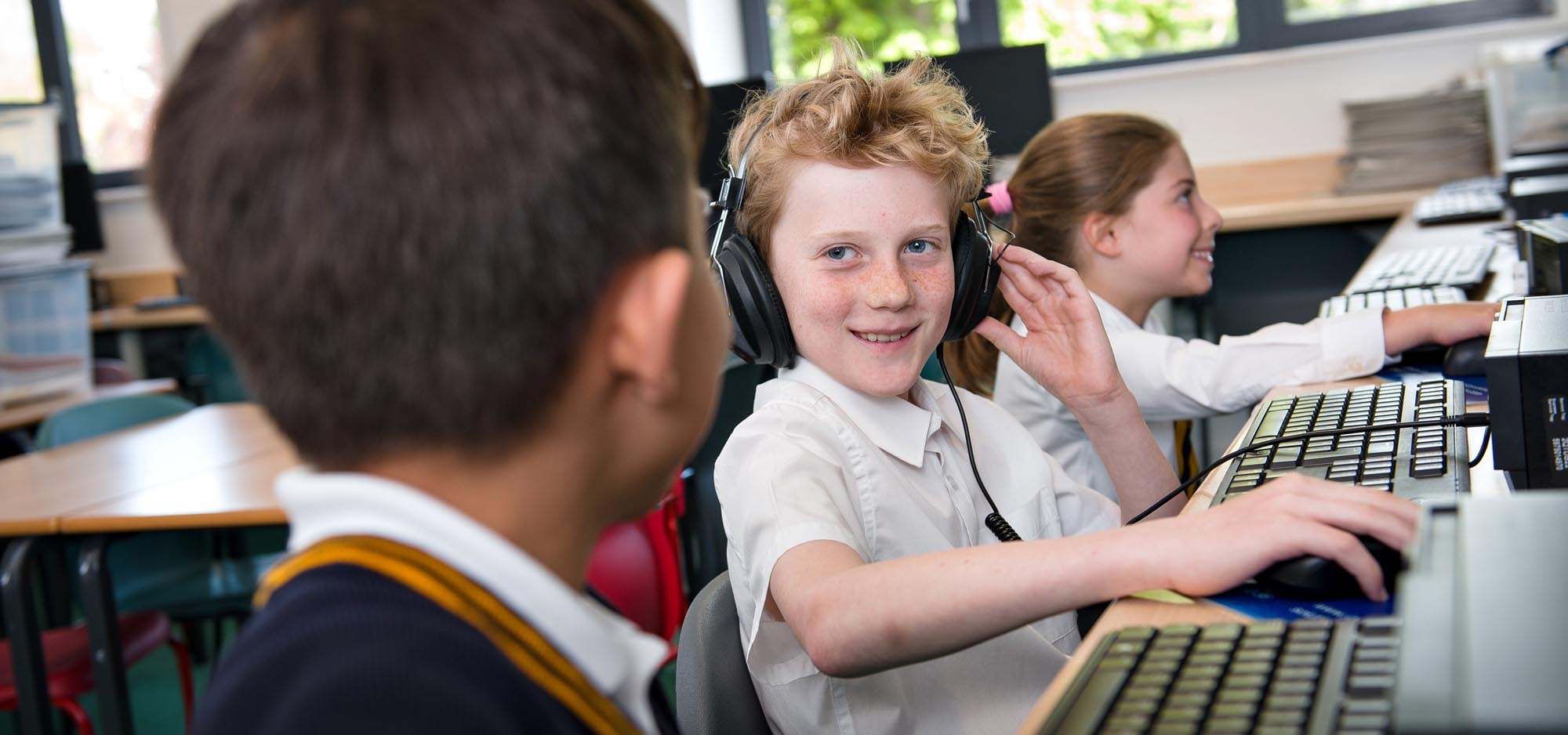 Boy with headphones by computer
