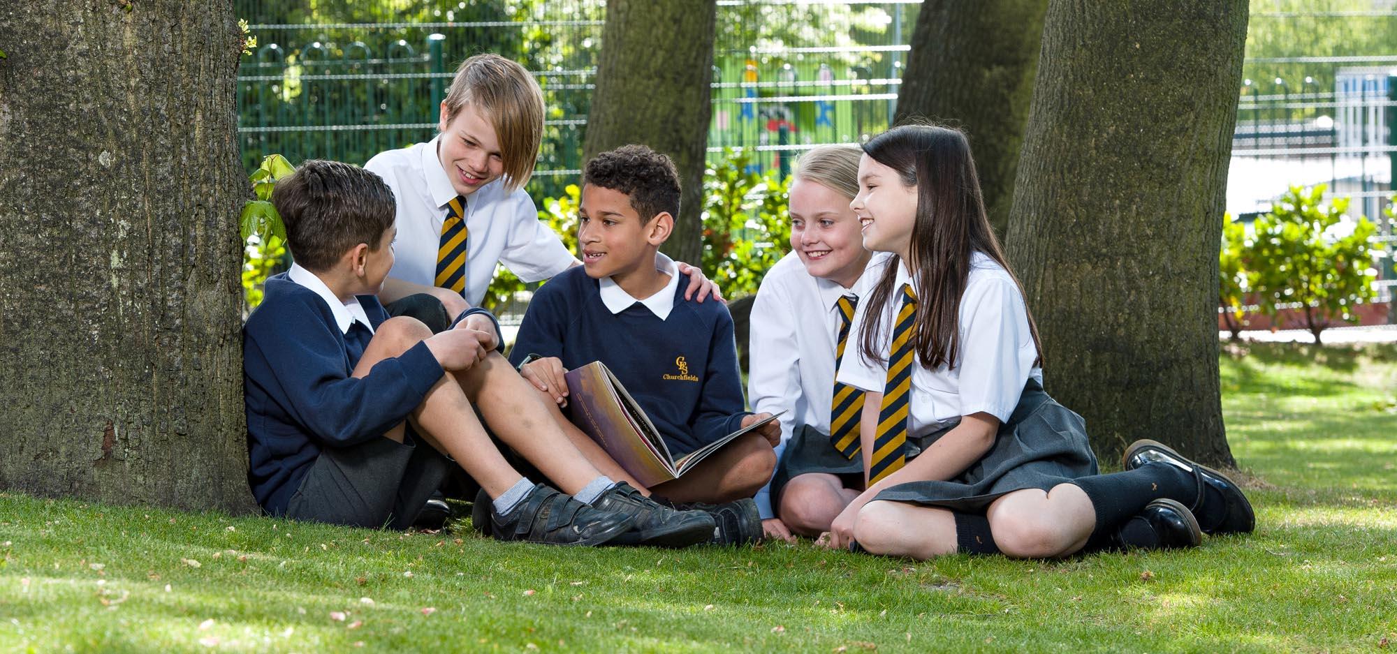 Group of children sitting under tree