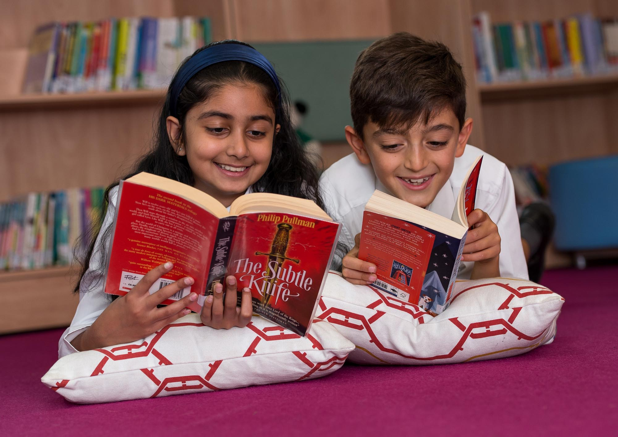 Boy and girl lying on cushions reading books