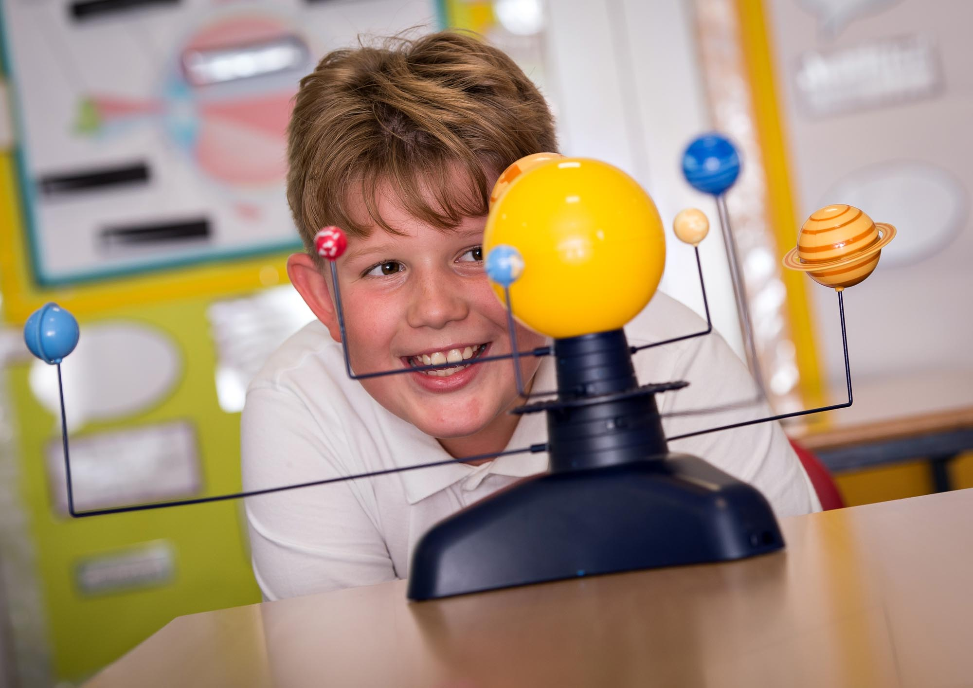 Boy looking at solar system model