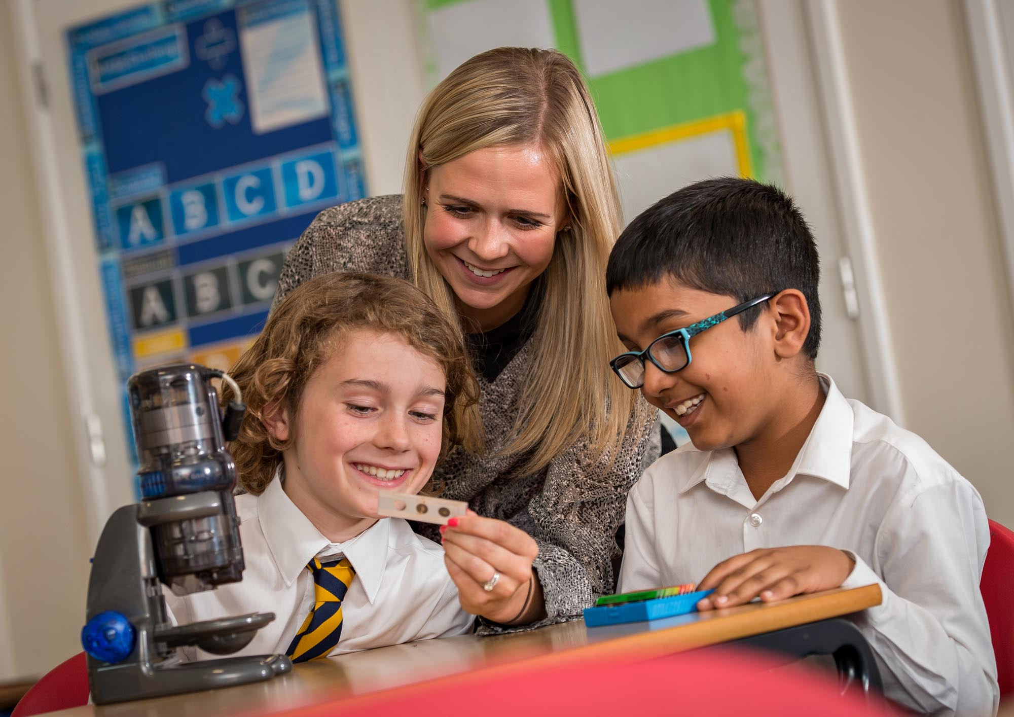 Teacher looks at science slides with two pupils