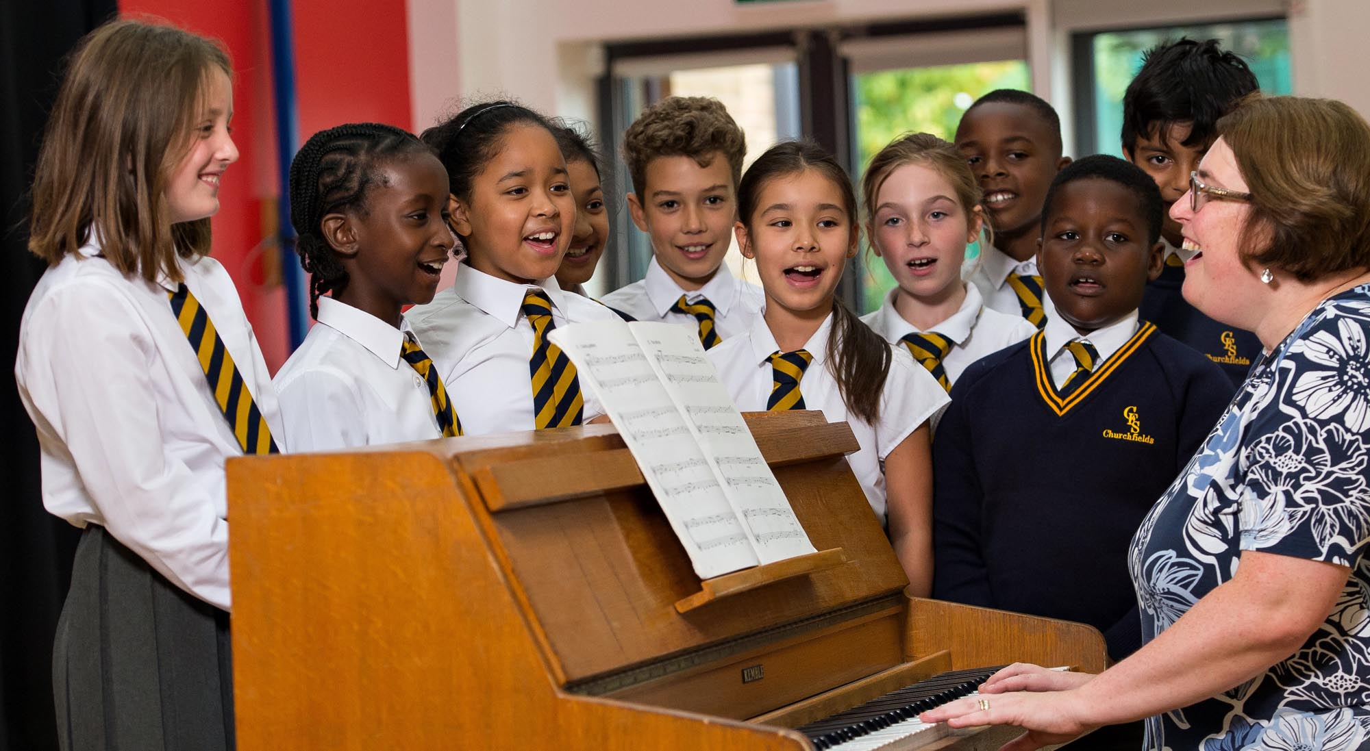 Mrs Emeny playing the piano with a group of pupils singing