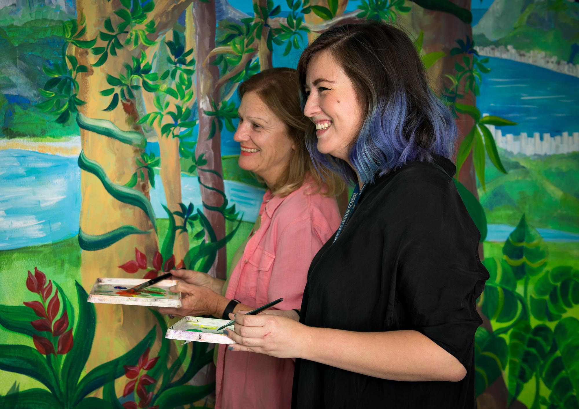 Mrs Thornton and Ms Garcia holding brushes and paint next to wall painting