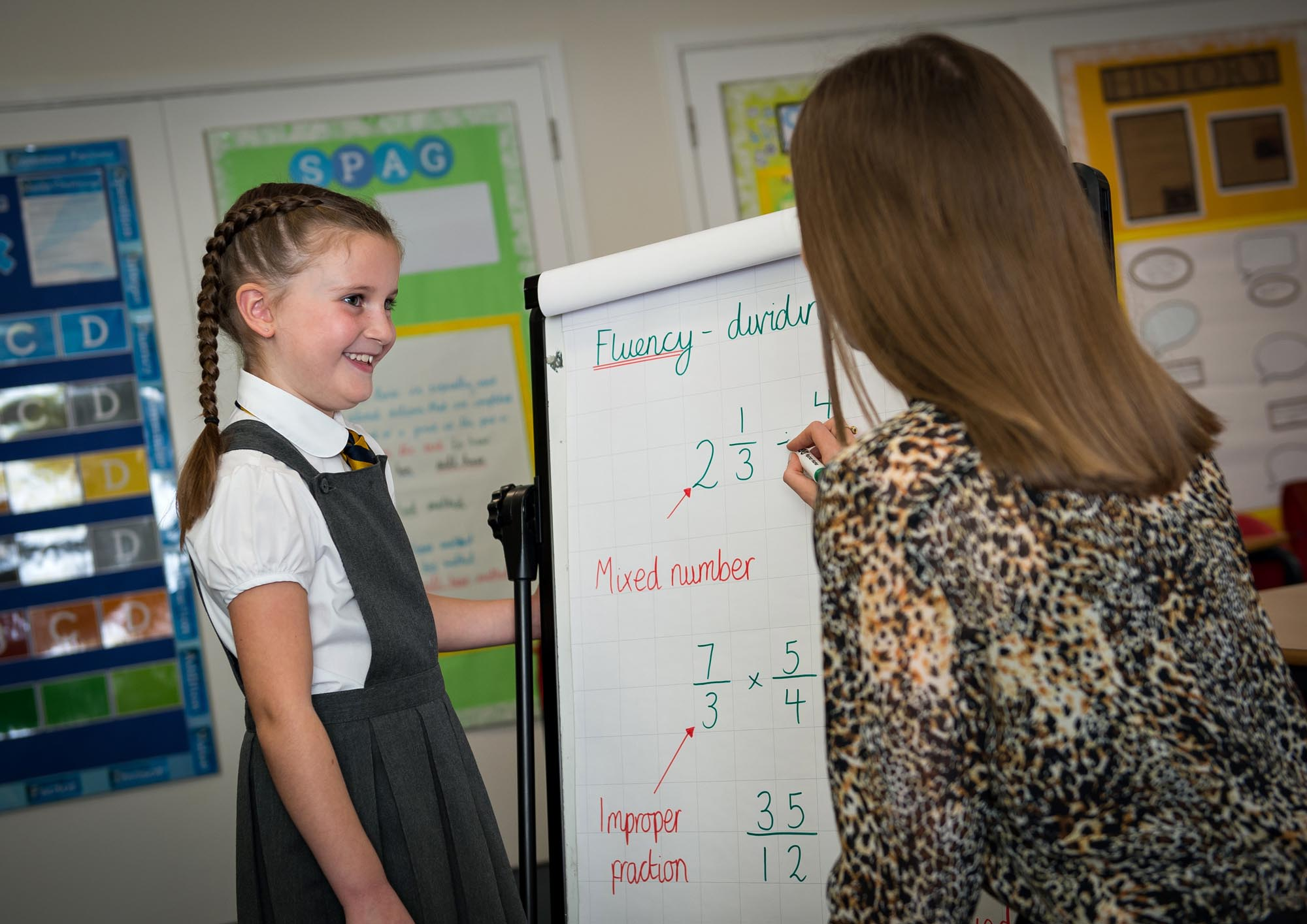 Child looking at a flipchart with a teacher