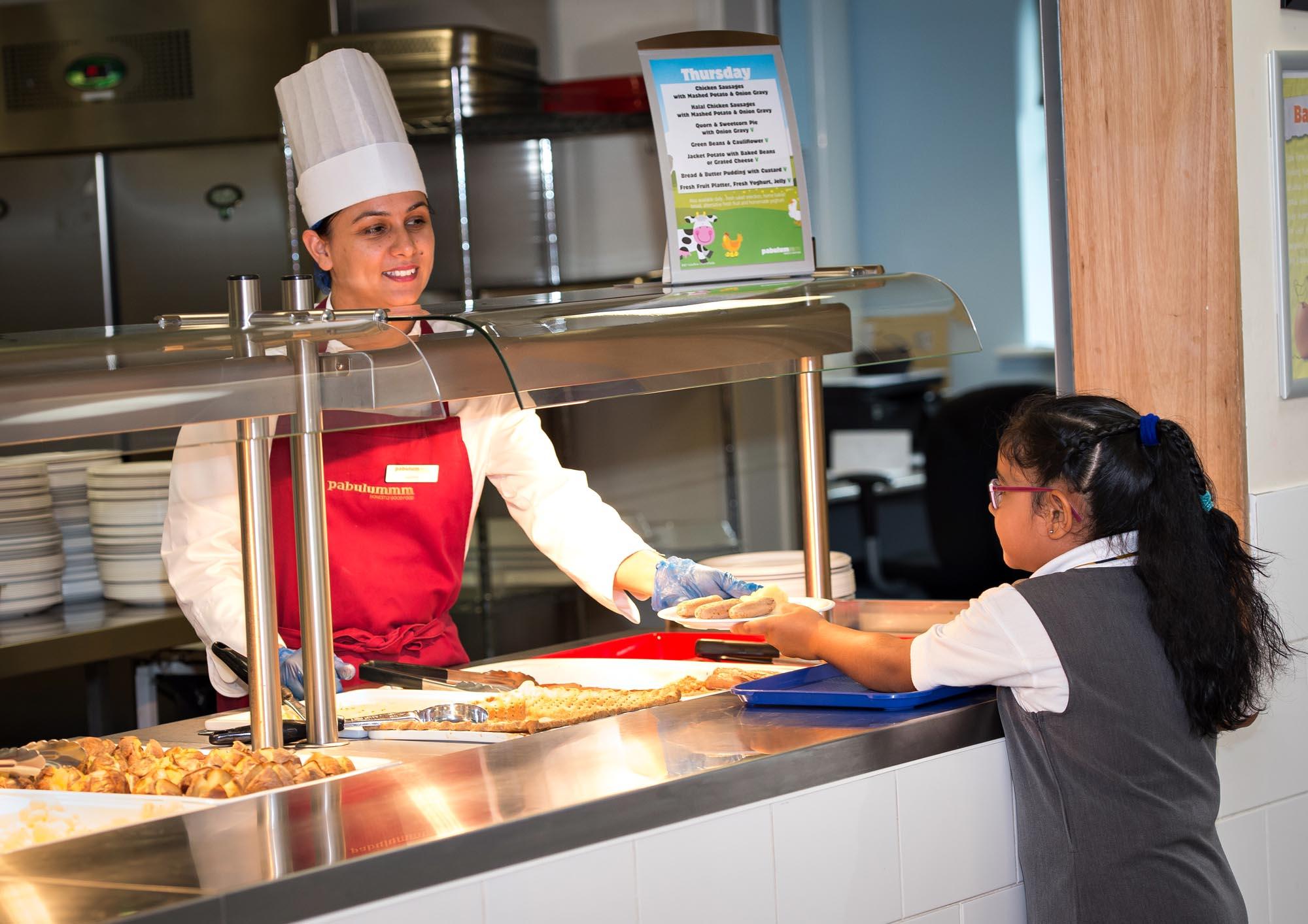 Girl being served dinner by kitchen staff