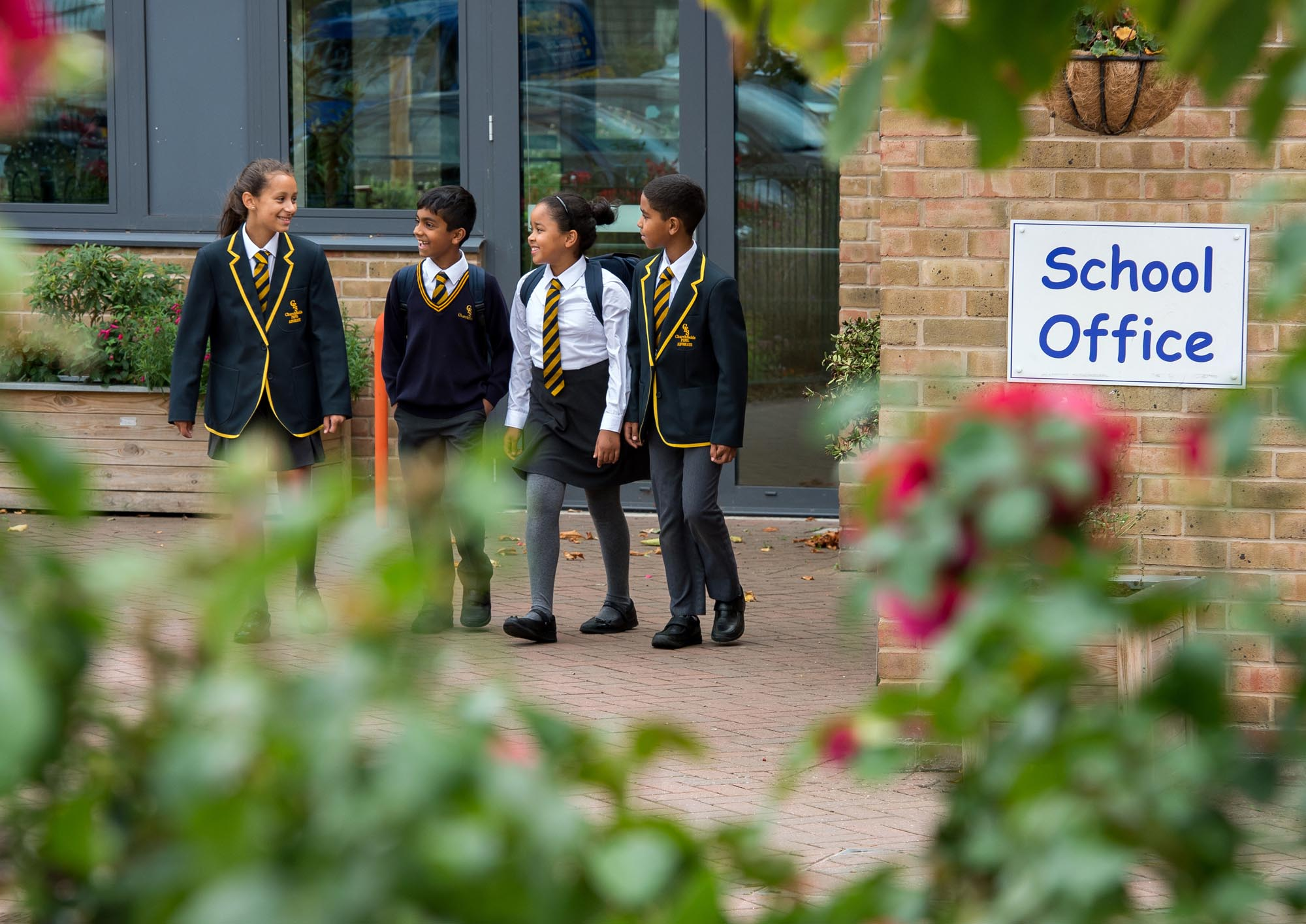 Group of children walking out of School framed by flowers