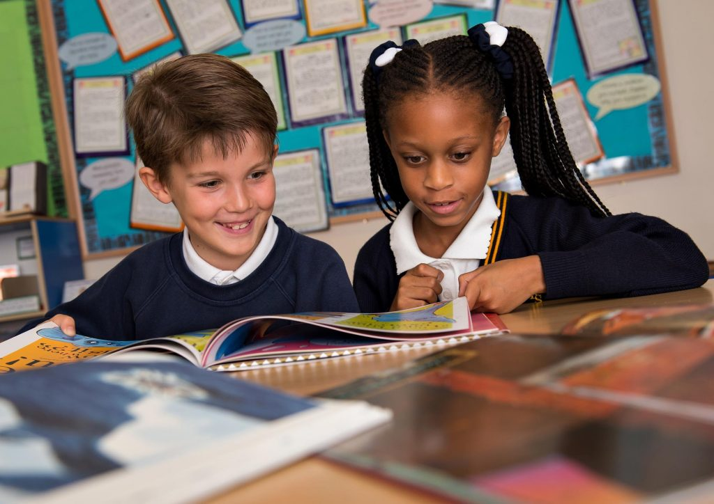 Boy and girl reading book together