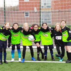 Girls football team posing in front of goal